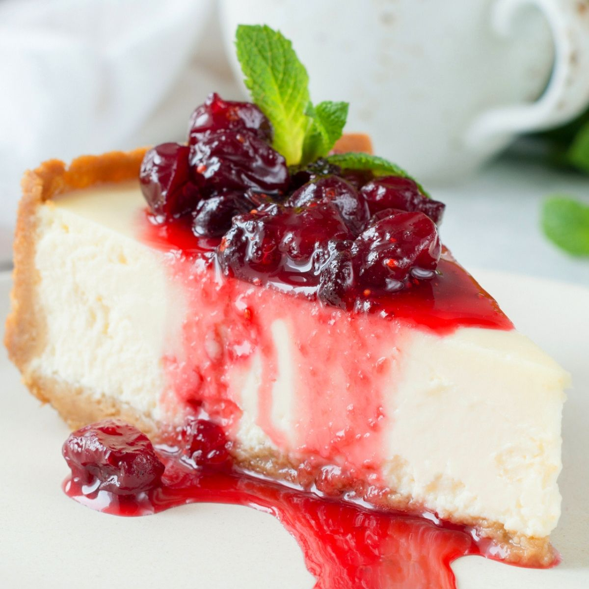 Slice of cheesecake topped with cherries and mint leaf
