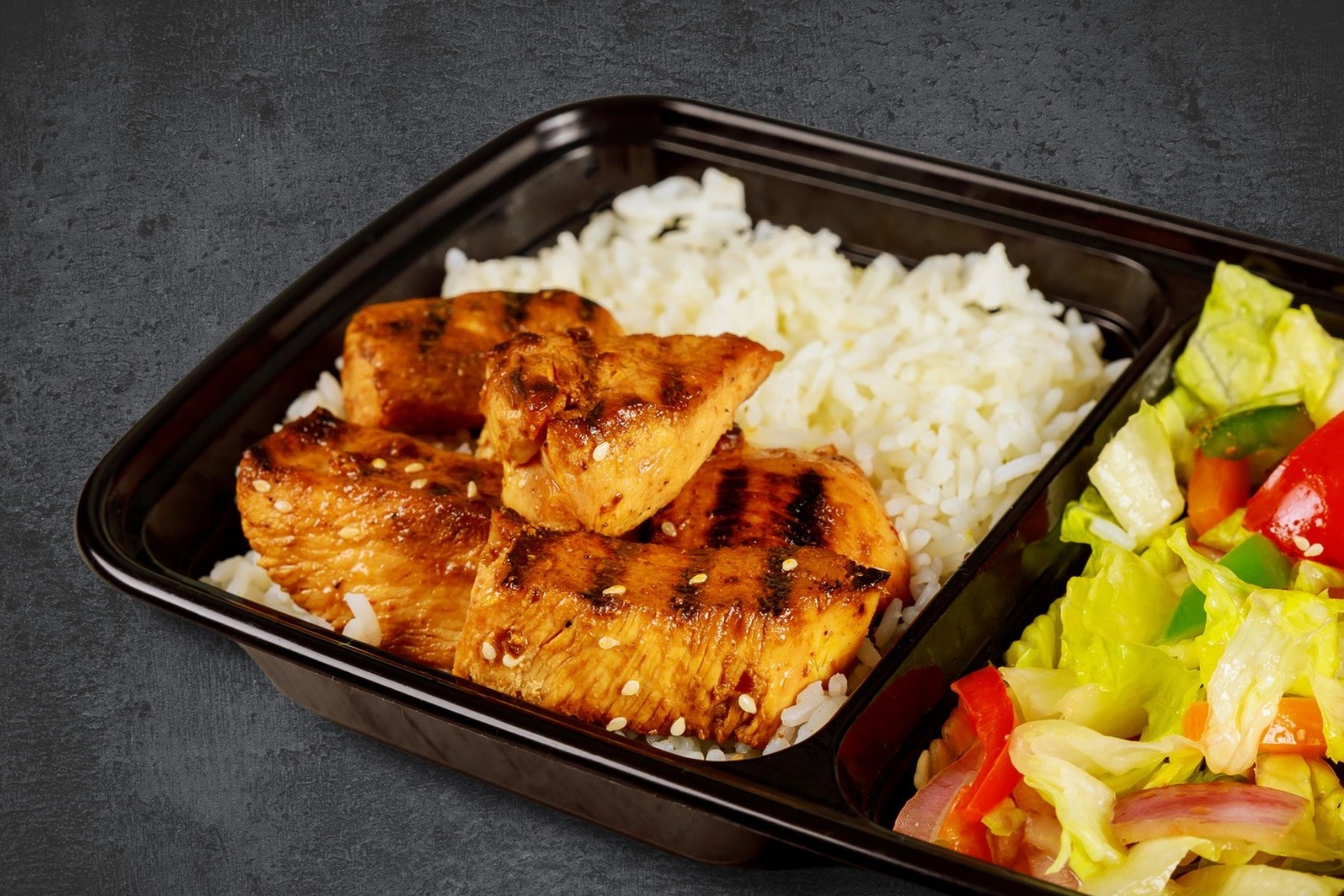 image of an individual size takeout container with grilled chicken on top of a bed of white rice and a side of tossed salad