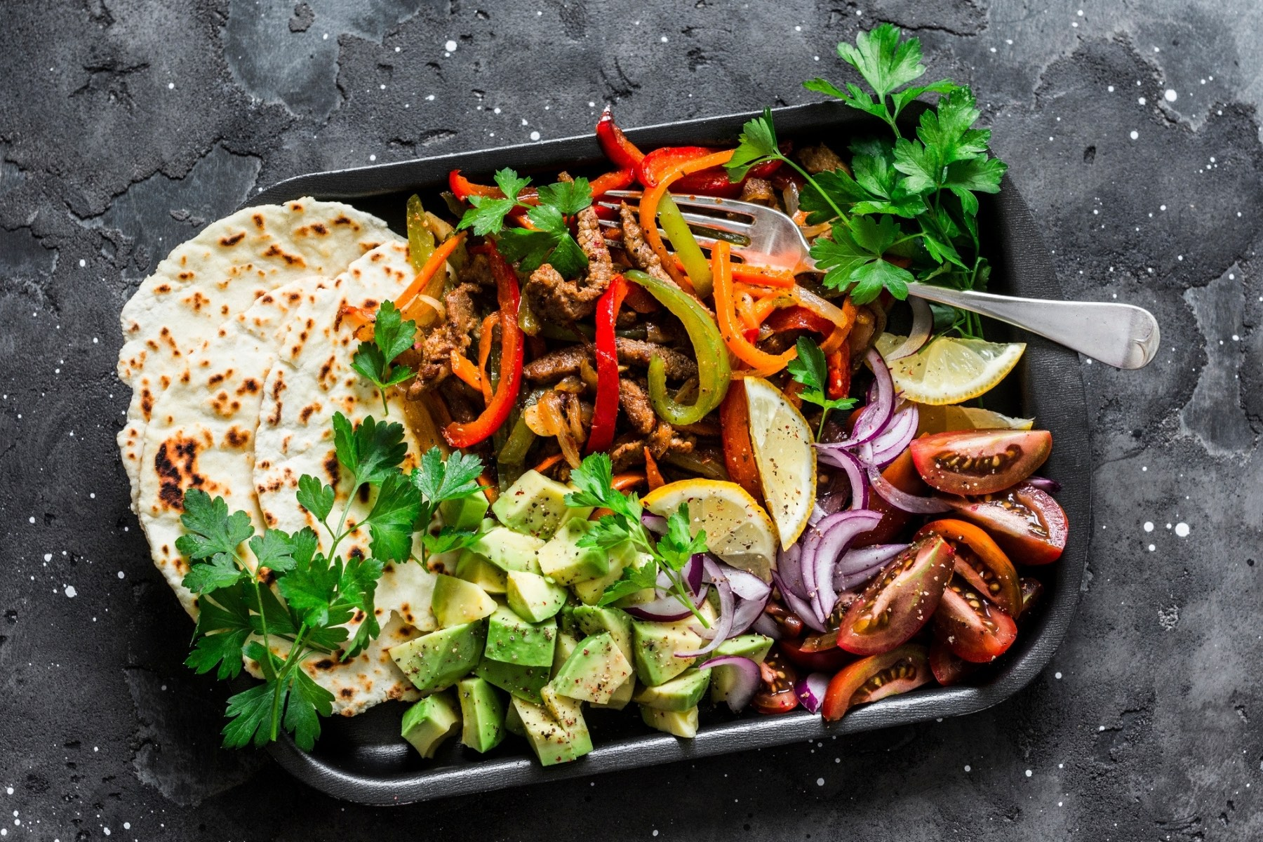 Image of ingredients to assemble a fajita, including beef strips, grilled peppers, tomato wedges, cubes of avocado and tortilla wraps in a takeout container