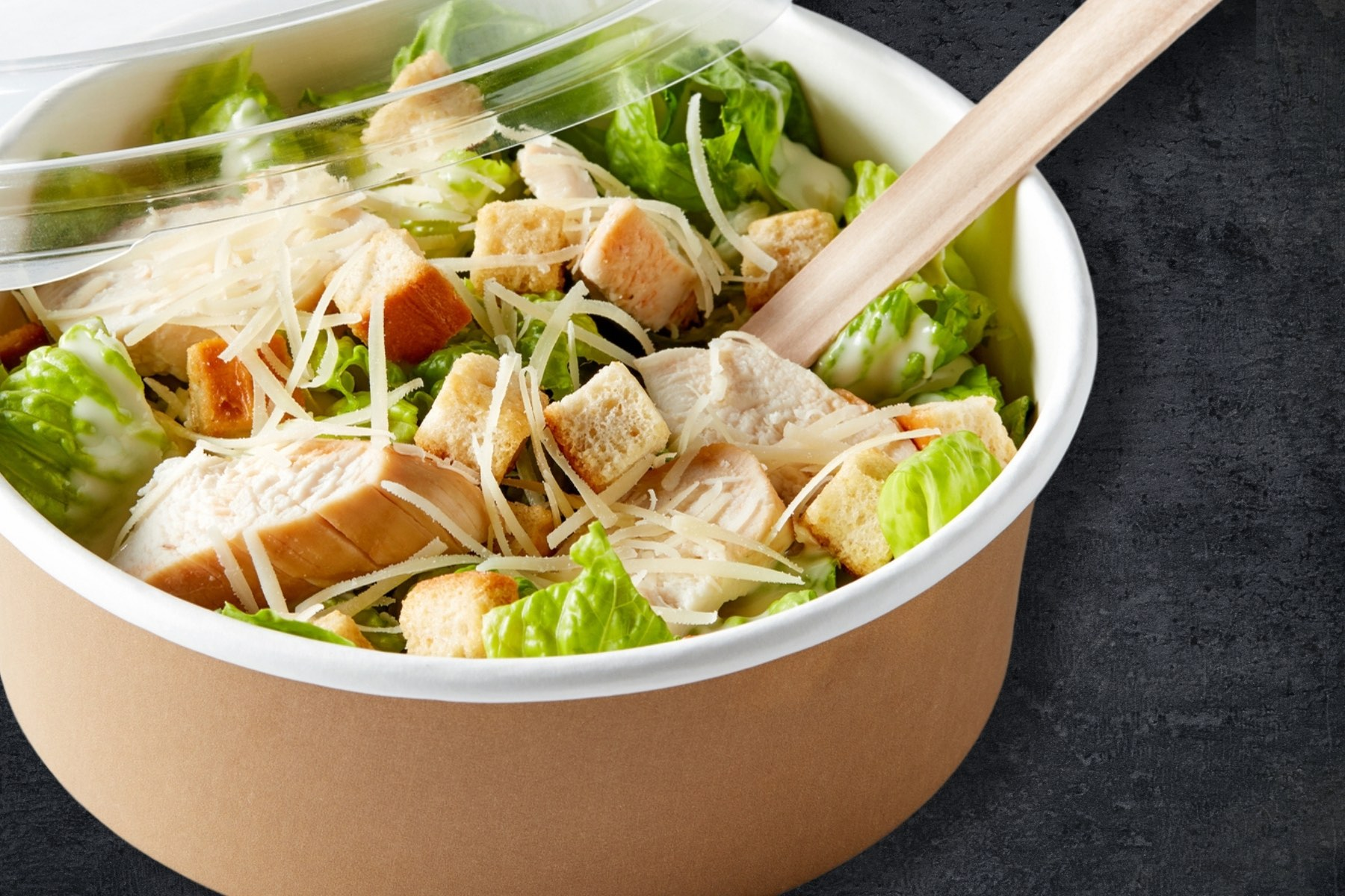 Image of a single serving of caesar salad in a takeout container